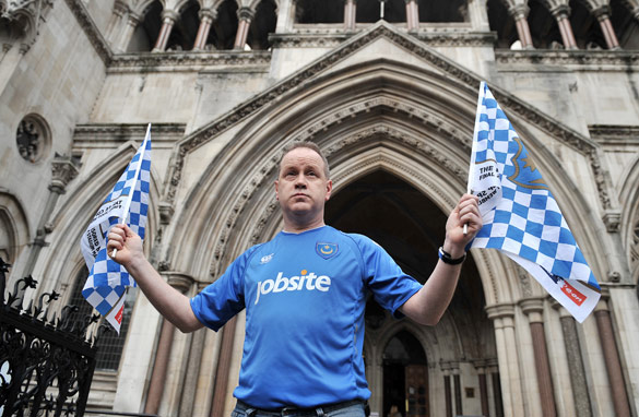 A lone Portsmouth fan stands outside the London High Court waiting for news on his beloved club.