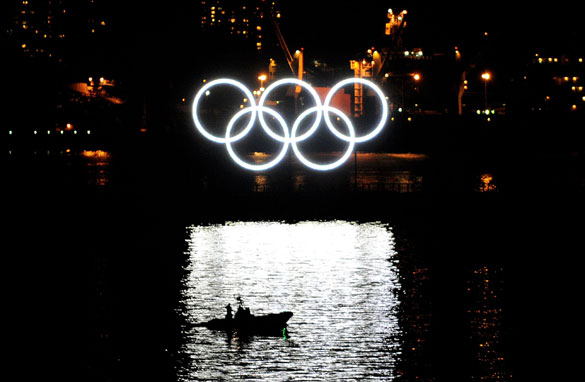 Olympic rings light the Vancouver harbour while fear mounts that increased security will strangle the spirit of the games.