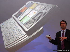 Microsoft's Robbie Bach demonstrates a new phone with the company's new operating system.
