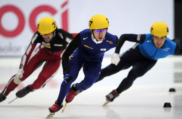 South Korean Jung-Su Lee crosses the finish-line ahead of Canada's Charles Hamelin and American speedskating legend Apolo Anto Ohno.