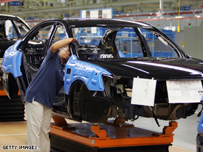 Hyundai employees work on a car on the assembly line at the Montgomery, AL plant