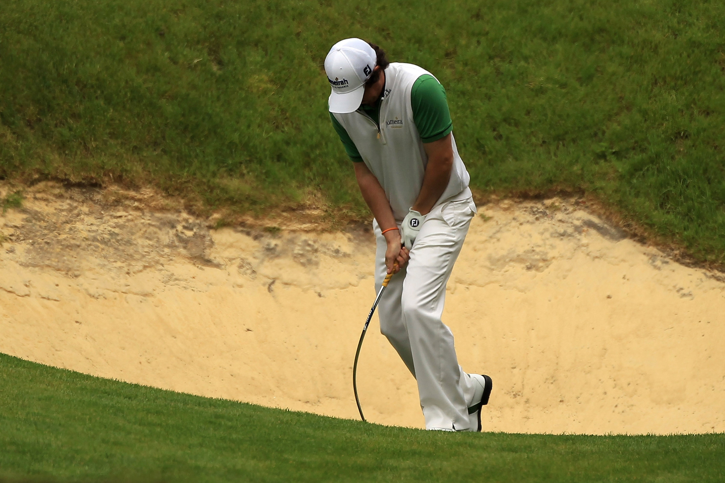 Rory McIlroy damages his club after getting stuck in the sand on the 10th hole.