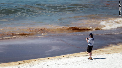 An EPA worker takes photos of oil coming ashore in Orange Beach, Alabama.