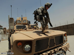 A soldier from the 10th Mountain Division walks down a vehicle in Afghanistan. A new poll indicates most Americans support President Barack Obama's timetable for withdrawal.