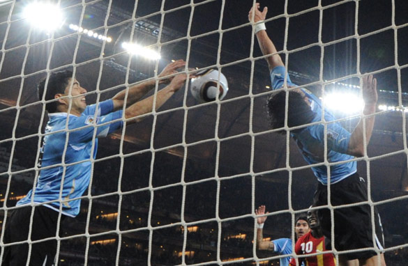 Luis Suarez, left, uses his arms to deny Ghana a dramatic late winner on Friday night. (AFP/Getty Images)