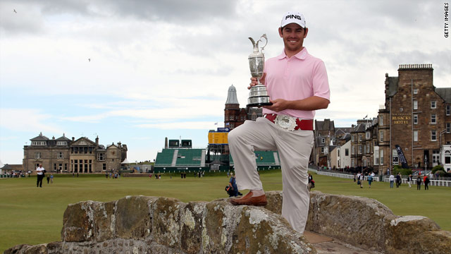 The new champion proudly displays the Claret Jug while standing on the Swilcan Bridge.