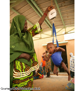 A community health volunteer weighs 12-month-old Mariam at a health center in Koma Bangou, Niger.  Mariam lives with her 19-year-old mother, Baraka, nearby.  Baraka said she cried when she found out her daughter was severely malnourished. She said she would like to feed her child but often has no food to give her.