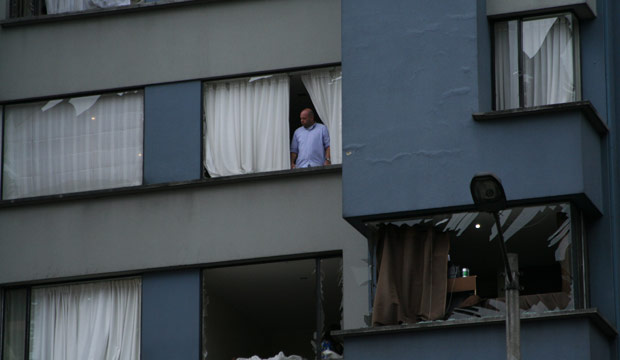 Man looks out shattered apartment window