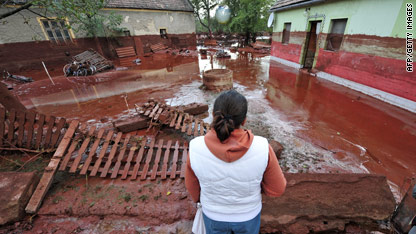 A woman surveys the damage in Devecser, Hungary after the village was floodedby toxic red sludge from a local aluminium plant.