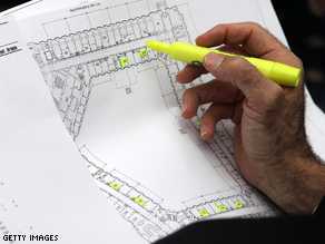 A man highlights vacant offices on a floor plan during an office selection lottery for new House of Representatives members.