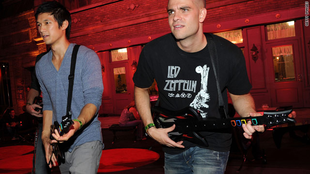 """Glee's"" Harry Shum Jr. and Mark Salling play ""Guitar Hero"" at an event."