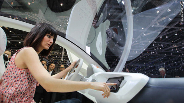 A model tries out the iPad controls of a Tata Pixel at the Geneva motor show.