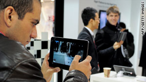 Visitors test a tablet during the 2011 Mobile World Congress in Barcelona, Spain, on February 17.