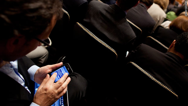 A man checks what appears to be an iPhone while attending a Senate privacy hearing with Apple and Google executives.
