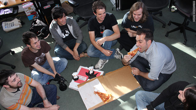 Reddit developers, including general manager Erik Martin with pizza in hand, sit in their San Francisco office.