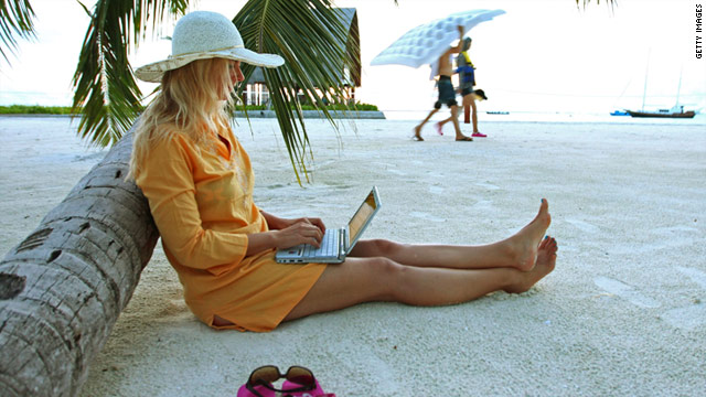 A woman browses the internet on a laptop while on the beach at Villingili Island, part of Maldives.