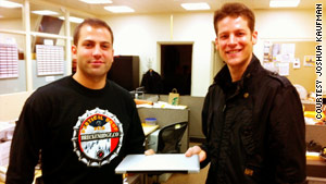 Joshua Kaufman, right, gets his stolen laptop back on Wednesday from the Oakland police.