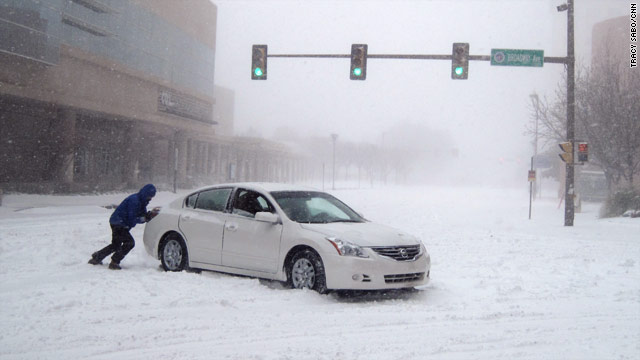 A man tries to push a car in Oklahoma City.