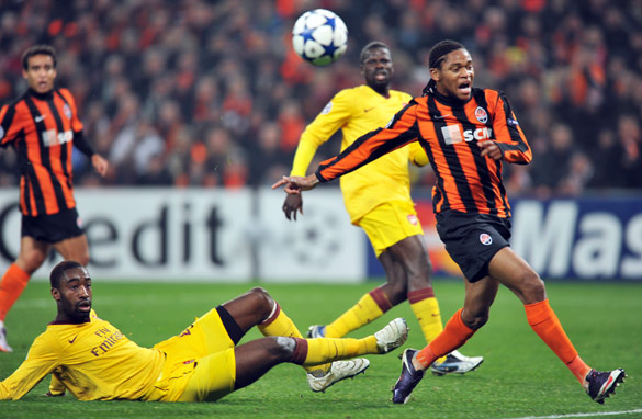 Shakhtar's Brazilian forward Luiz Adriano, right, is challenged by Arsenal's Switzerland defender Johan Djourou.
