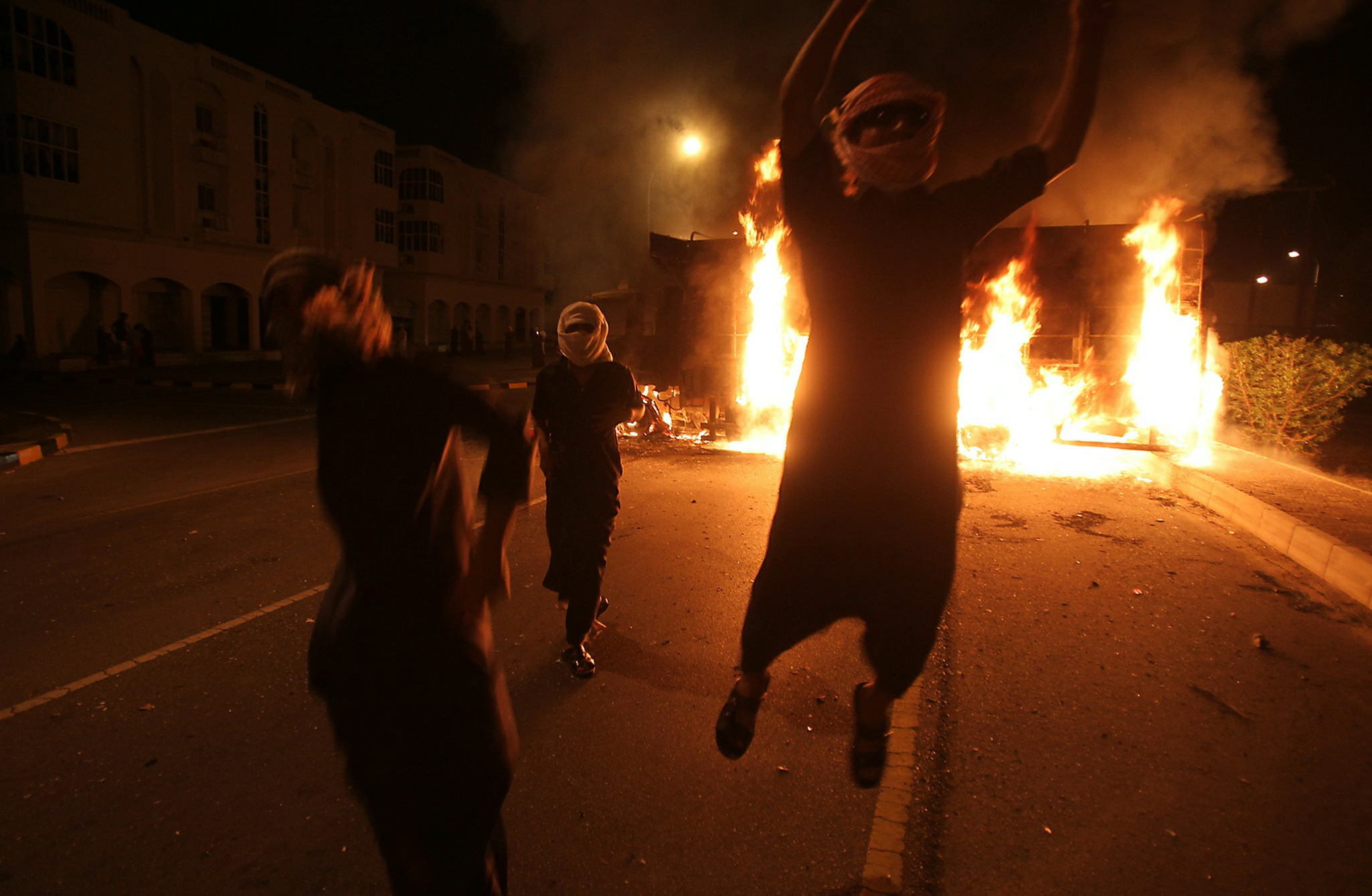 Masked Omani protesters jump in front of burning vehicles during a demonstration in Sohar, more than 200 kms (125 miles) northwest of Muscat. Getty Images/AFP.