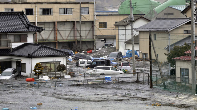 A tsunami smashes vehicles and houses at Kesennuma city in Miyagi prefecture, northern Japan.