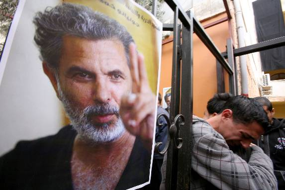 Palestinian youths mourn the death of Arab-Jewish actor and director Juliano Mer-Khamis (poster) outside The Freedom Theatre in Jenin refugee camp in the West Bank