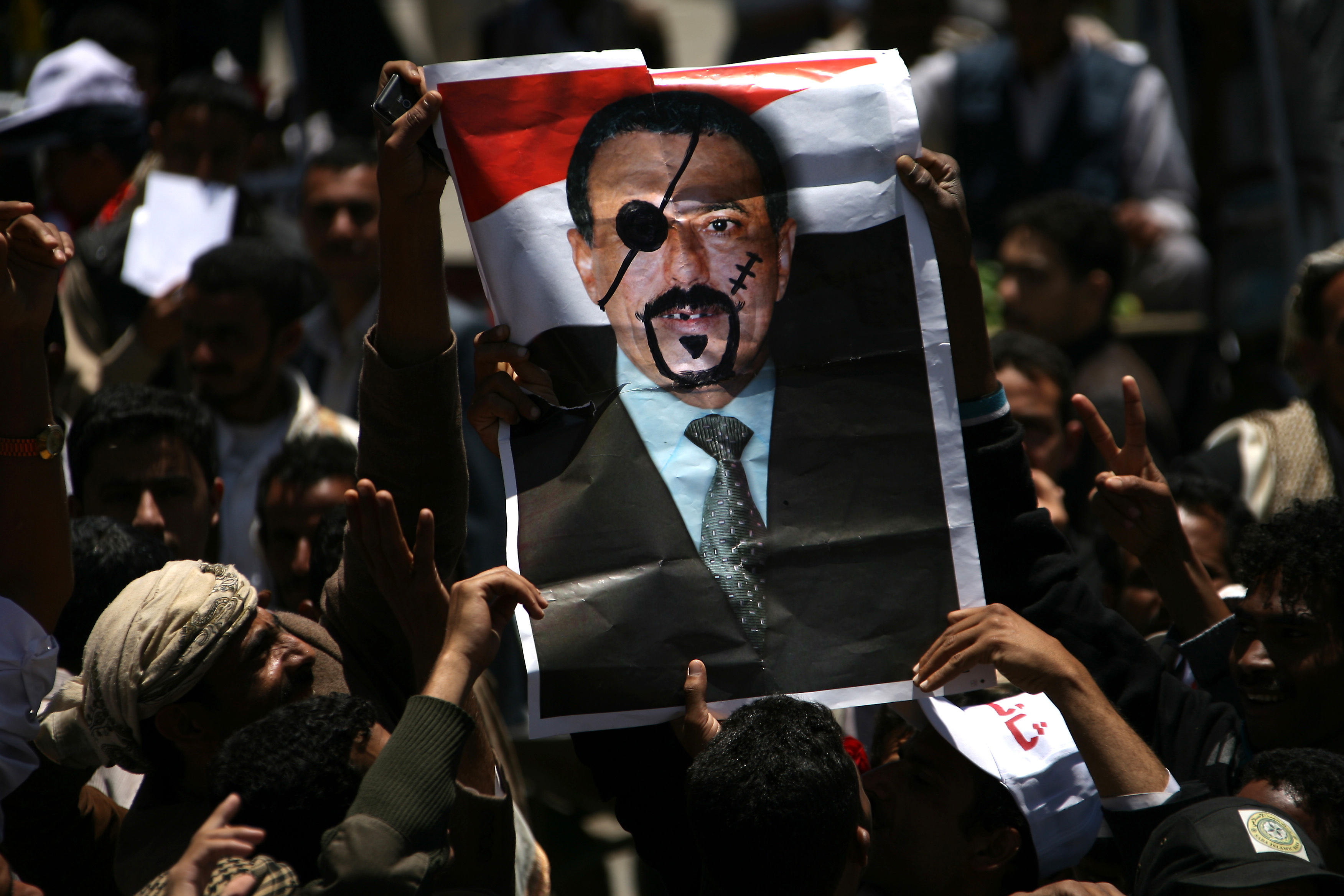Yemeni anti-government protesters hold a picture of President Ali Abdullah Saleh depicting him as a pirate during a demonstration calling for his ouster in Sanaa.