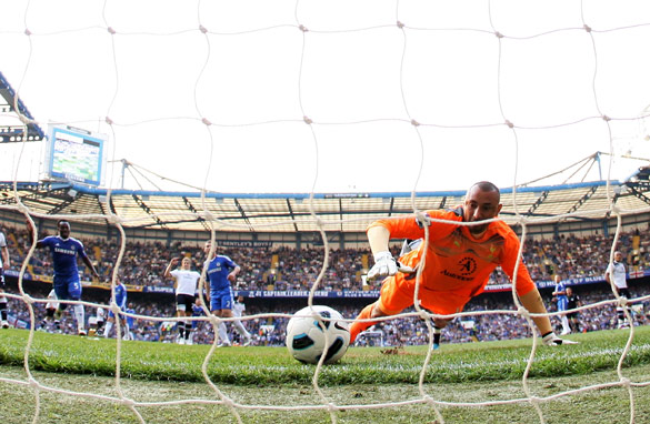 Heurelho Gomes scrambles to try and prevent Frank Lampard&#039;s shot from creeping over the line.