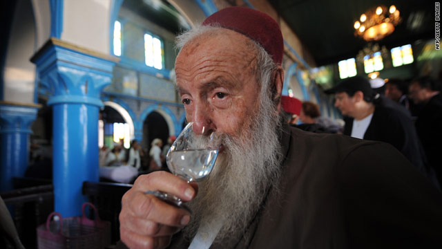 A rabbi drinks a glass of fig alcohol at the 2010 pilgrimage to Derba, a Tunisian island