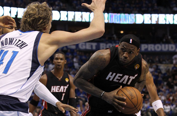 LeBron James of the Miami Heat drives in vain against the Dallas Mavericks&#039; Dirk Nowitzki.