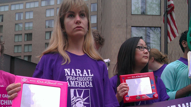 Abortion rights activists Etch A Sketch against Romney