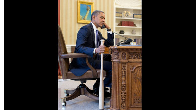 Obama speaks with world leader on phone while holding baseball bat