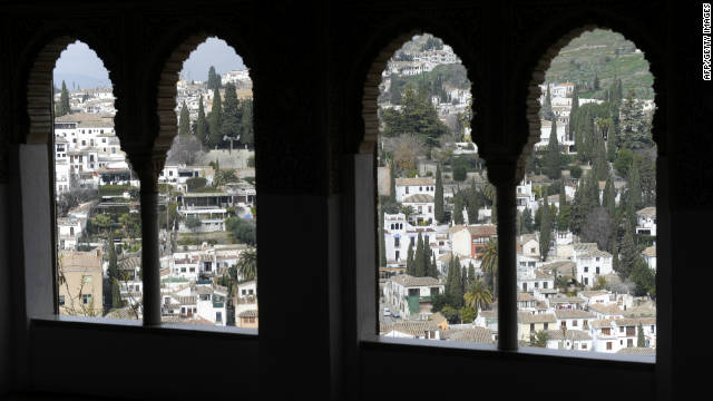 A view through pointed windows to the city of Granada.