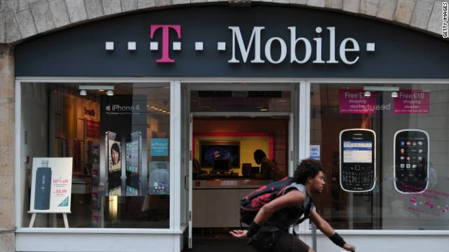 A biker rides past a T-Mobile store in London.