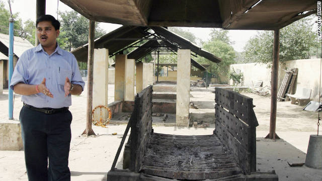 "Anshul Garg, director of Mokshda, next to the group's ""Green Cremation System."" The NGO says its system reduces greenhouse gas emissions from burning wood by up to 60%."