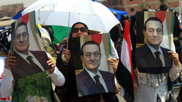 Supporters of former Egyptian president, Hosni Mubarak hold up posters of him outside the Cairo criminal courts on August 15.