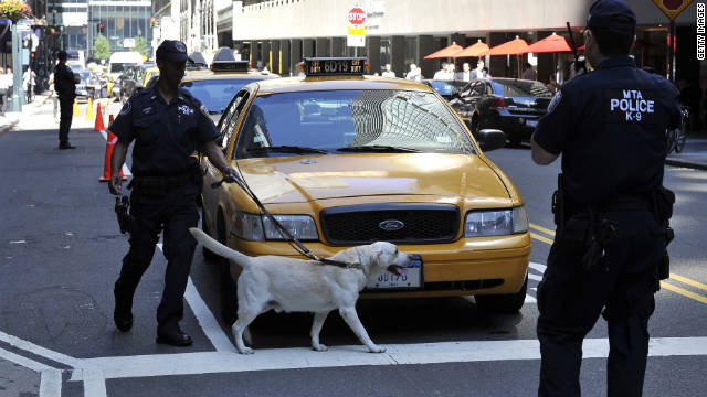 A canine unit police officer inspects cars Friday outside Grand Central Station in New York.