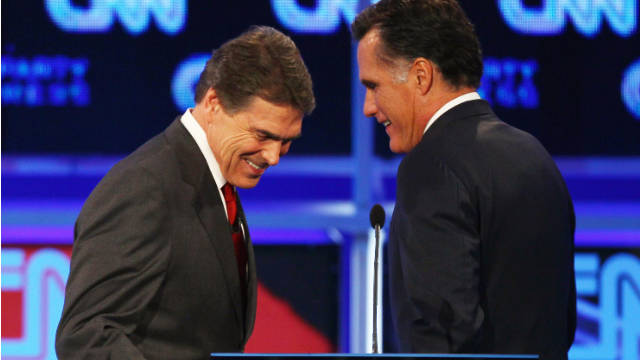 Mitt Romney, right, walks past Gov. Rick Perry during a break in the GOP debate sponsored by CNN and The Tea Party Express.
