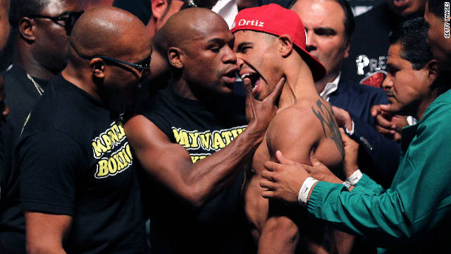Boxer Floyd Mayweather grabs Victor Ortiz after their weigh-in on Friday.