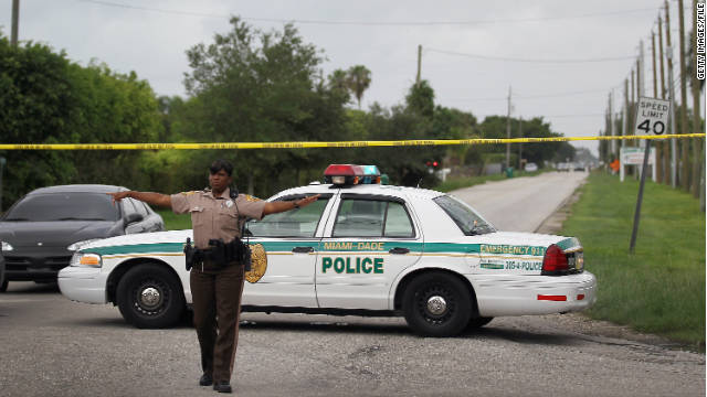 A Miami-Dade police officer directs traffic away from a crime scene in July.