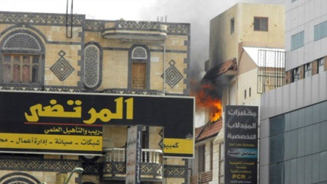 A residential building burns in Sanaa following clashes between protesters and government forces.