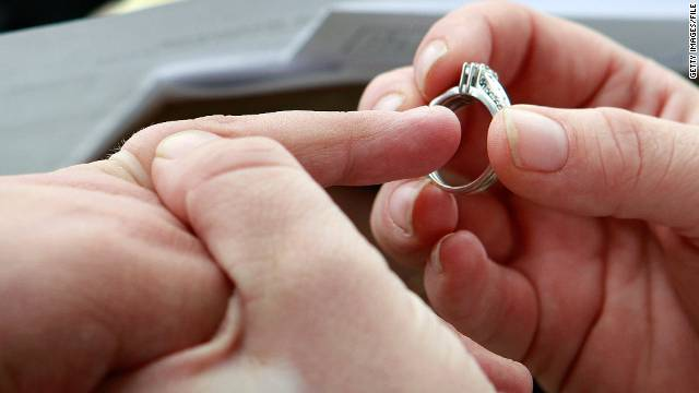 Jodie Vandermark-Martinez slides a ring on her partner, Jessica Vandermark-Martinez, during their wedding ceremony in Iowa.