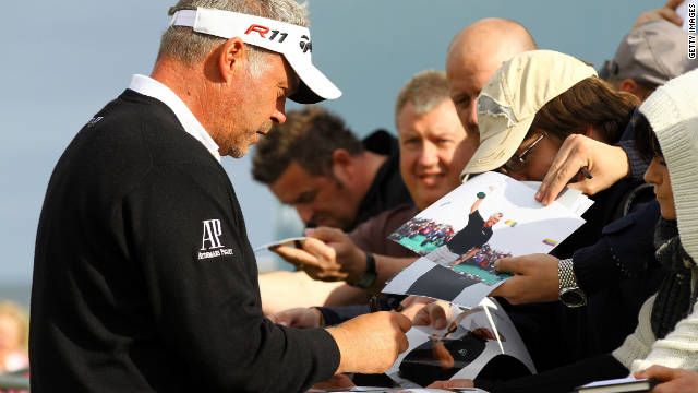 Reigning British Open champion Darren Clarke signs autographs before his practise round.