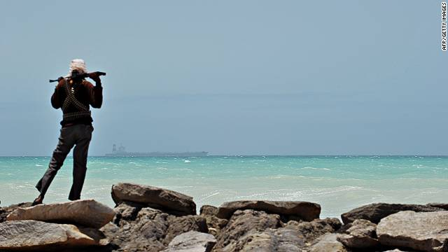 A pirate stands on a rocky outcrop on the coast of Hobyo, central Somalia