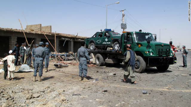 Members of Afghanistan National Police and security officials clear debris after the blast in Lashkar Gah.