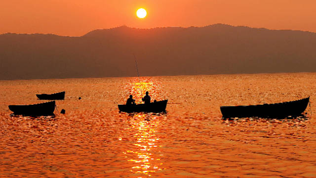 Two people fish on a boat on Macedonia's Lake Ohrid, one of the deepest and oldest freshwater lakes in Europe.
