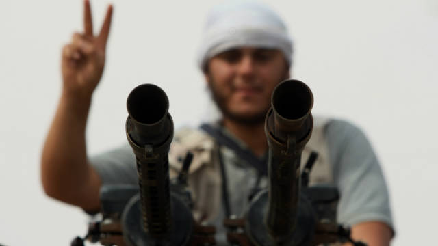 A National Transitional Council fighter flashes the V-sign as on the eastern front line of Sirte on October 2