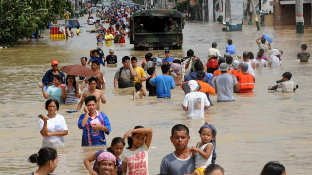 Residents of the Filipino town of Calumpit wade through murky water in the aftermath of Typhoon Nalgae which tore across the East Asian country Saturday