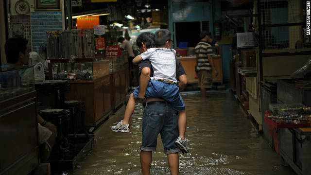 A man carries a boy on his back at a flooded market in a low-lying area of downtown Bangkok on 4 October.