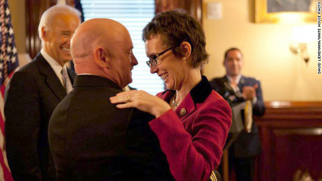 Navy Capt. Mark Kelly hugs his wife, U.S. Rep. Gabrielle Giffords, after receiving the Legion of Merit from Vice President Joe Biden during his retirement ceremony Thursday in Washington.